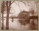 W. H. Best crossing flooded intersection of 8th Street S. and 2nd Avenue S. during flood of 1897, Fargo,