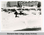 Bismarck Junior College students shovel car out of snowbank, Bismarck, N.D.