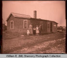 Family standing outside home, Williston, N.D.