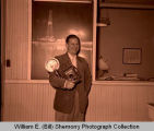 William E. (Bill) Shemorry portrait in front of oil discovery reflection photograph