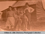 Family outside home, N.D.