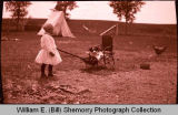 Girl with dog in wagon, N.D.