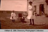 Girls with puppy in wagon, N.D.
