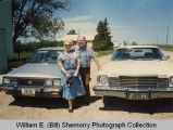 William E. (Bill) and Glo Shemorry by cars