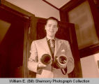 Jim Snyder holding projection lenses, Williston, N.D.