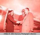 Tony Thomas and Don Carlson greet man in front of airplane, Williston, N.D.