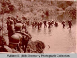 United States soldiers ford jungle stream in Burma