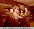 Williston Fire Department firemen with Bus McCrory in fire station, Williston, N.D.