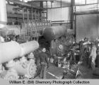 Oil refinery or plant interior, workers supervising equipment, Williston Basin, N.D.