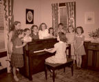 Girls singing at piano, Williston, N.D.