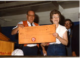 Man and woman holding a $1,000 check to the Williston Volunteer Fire Department, Williston, N.D.
