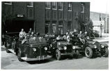 Williston firemen with three fire engines in front of the Williston Fire Department, Williston,...