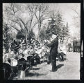 Man in military uniform conducting a band outside, Williston, N.D.