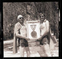 Two men holding a first place trophy for a swimming air mattress competition, N.D.