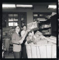 Two men looking at boxes in a mail cart, N.D.