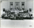 Group portrait outside the Firemen's Convention Hall, Bottineau, N.D.