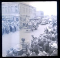Crowd of people watching a tractor drive down Main Street, Williston, N.D.
