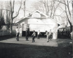 Children playing basketball outside on a driveway, N.D.
