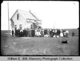 Large group in formal dress at Bauste homestead, Wildrose, N.D.