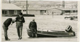 Three men by a boat while flood waters rise around homes, probably Minot, N.D.