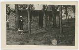 Woman in front of Theodore Roosevelt's log cabin on the State Capitol Grounds, Bismarck, N.D.