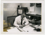 Charles Anderson at desk, Bismarck, N.D.