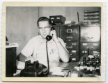 Charles Anderson at desk on phone, Bismarck, N.D.