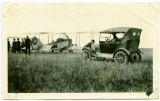W.R. Olson cranking his car next to airplane, Stanley, N.D.