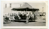 Children's merry-go-round with Shoberg Hotel in background, Sanish, N.D.
