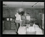 Two men talking with Gene Autry at Frank Wetzstein's cabin north of Mandan, N.D.