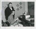 Two unidentified men with equipment in radio station, Rugby, N.D.