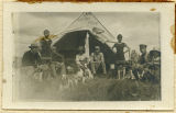 "Group photograph of camping or hunting group outside tent ""Camp Arrow Point"""