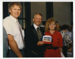 Governor George Sinner holding centennial hat with Doug Eiken and unidentified woman, Bismarck,...