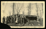 Group of men with rifles standing outside log house with dirt roof