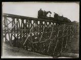 Laying rails for Minneapolis St Paul and Sault Ste. Marie Railroad over bridge, Kenmare, N.D.