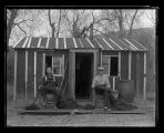 Two men seated in front of tar paper shack, Fort Berthold Indian Reservation, N.D.