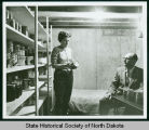 Man and woman in fallout shelter pantry, Bismarck, N.D.