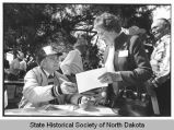 Arthur Link signing North Dakota Centennial logo for woman