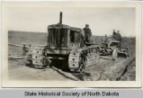 Civilian Conservation Corps members on tractor and grader working road surface
