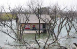 Man and house in floodwaters near Devils Lake, N.D.