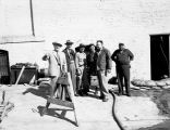 Men outside sandbagged building with pump line, Fargo, N.D.