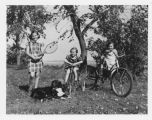 Louise Aandahl with tennis racket and Marilyn and Margaret Aandahl on bicycles on Aandahl farm, Litchville,