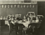 Students seated at table eating in classroom