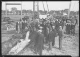 Flowing water from well demonstration with people looking on, McCarthy Well Co., Minneapolis, Minn.