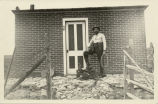 Man with foot on saddle by brick building, McKenzie County, N.D.