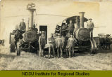 Men by steam engines pulling building