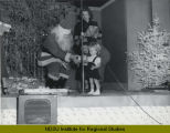 Child receiving gift from Santa Claus at Herbst Department store employee Christmas party