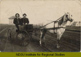 Two men in horse-drawn buggy with school in far distance.