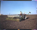 John Scott, Gilby, N.D. seeding crop in spring of year, tractor & drill with fertilizer attachment