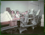 Girls operating butter cutting & wrapping machine at Mandan Creamery & Produce Assn.,...